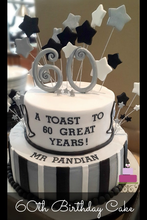 2 tier cake decorated in silver, black and white with a large number 60 topper and matching stars