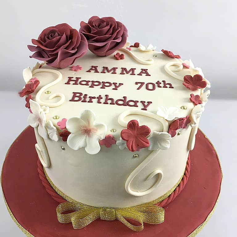 A round cake decorated with maroon and white fondant flowers and 2 large maroon roses.