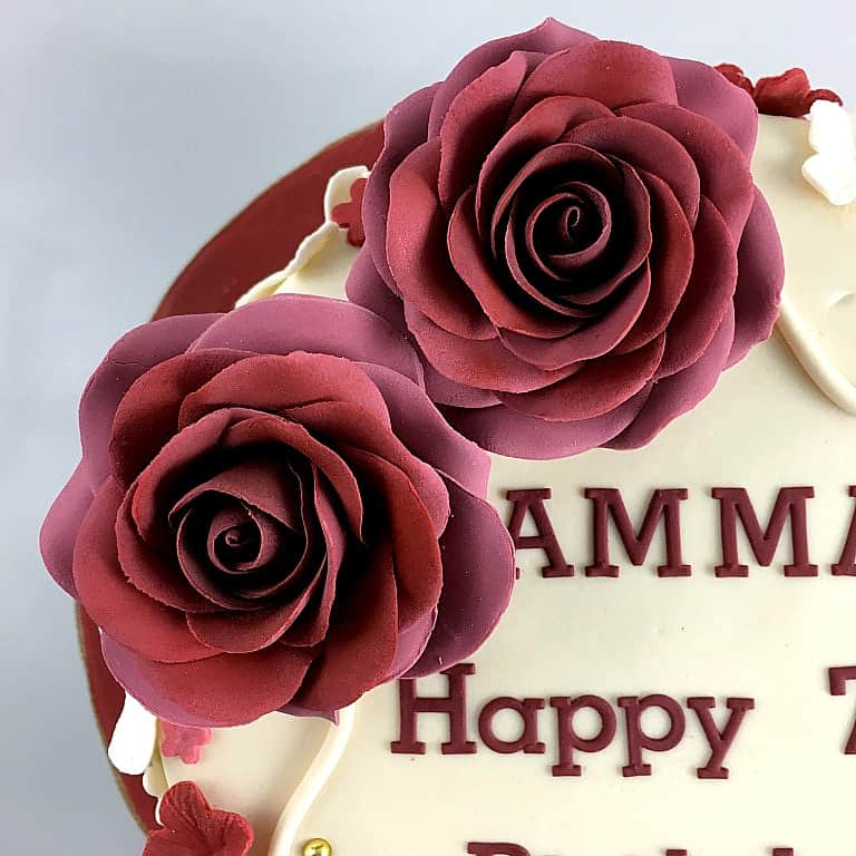 2 large maroon roses on a cake