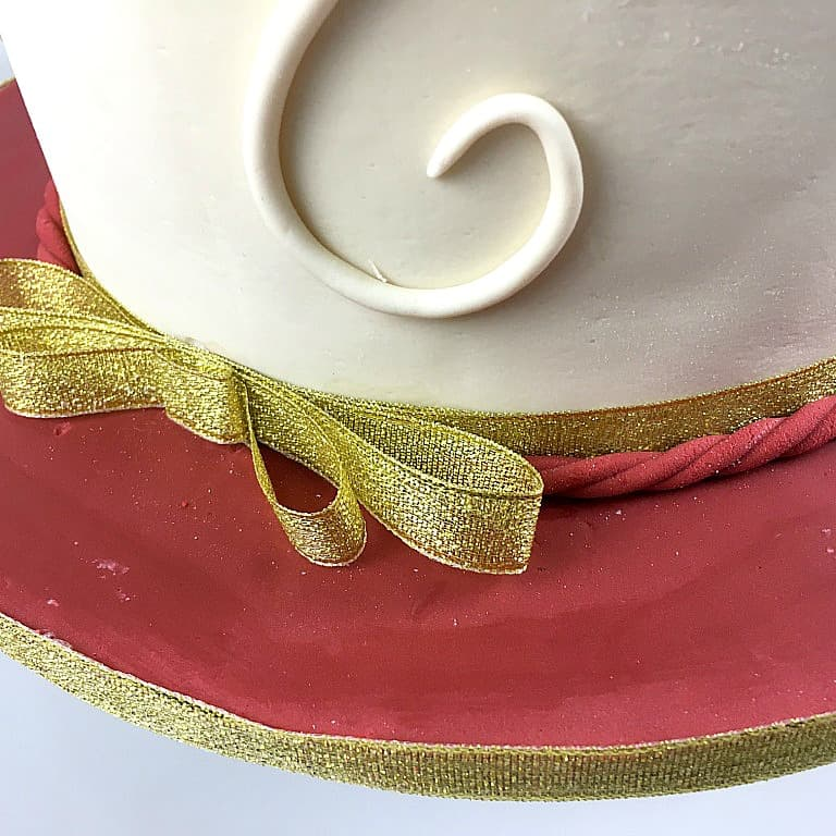Gold ribbon around the base of a cake