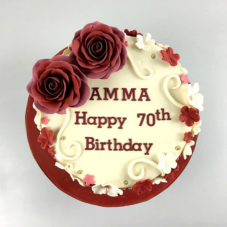 The top view of a round cake decorated with maroon and white fondant flowers and 2 large maroon roses.