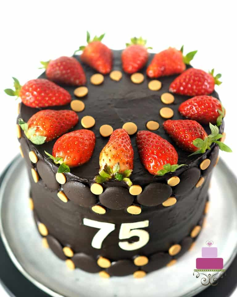 A 75th birthday cake in chocolate ganache decorated with fresh strawberries and butterscotch chips