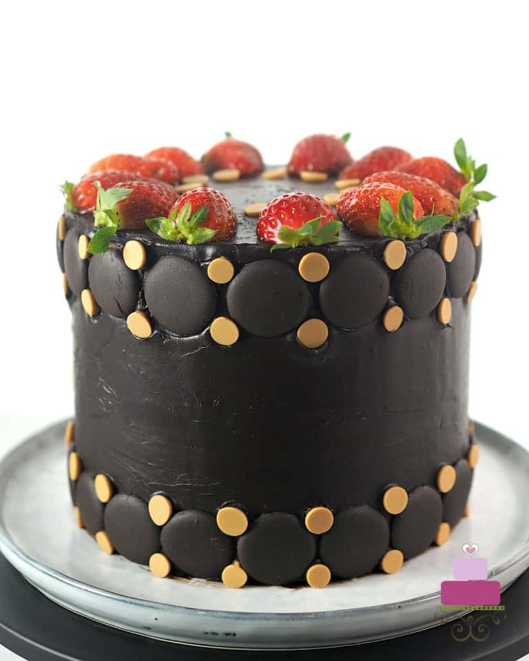 A round cake in chocolate ganache decorated with fresh strawberries and butterscotch chips