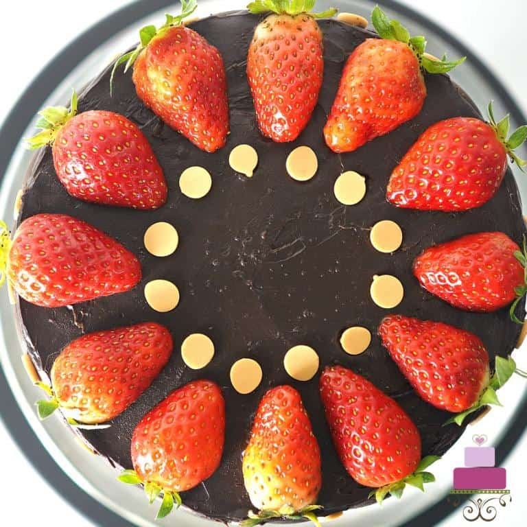 The top of a round chocolate cake decorated with fresh strawberries
