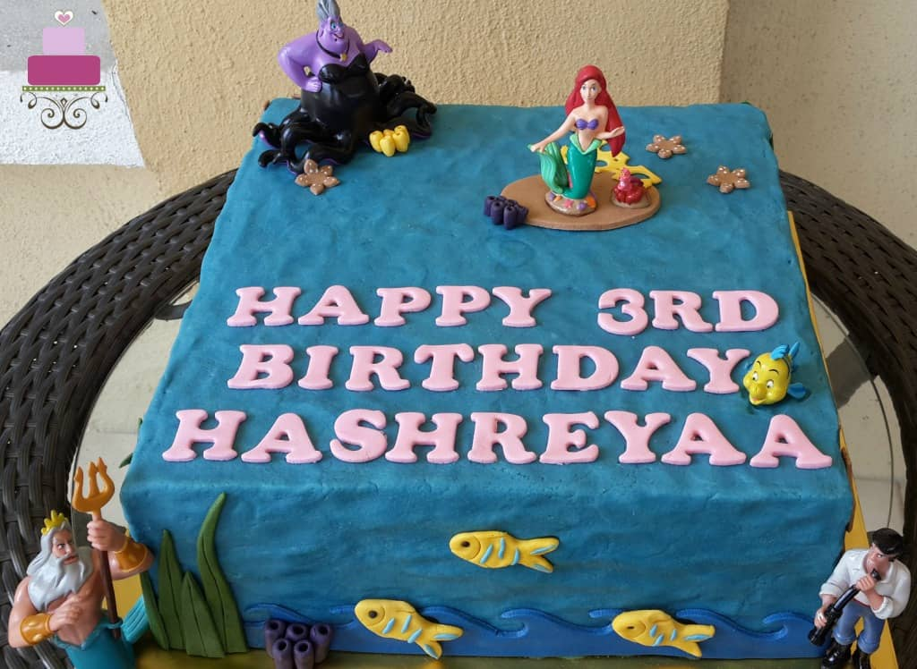 A square blue cake decorated with Ariel the Little Mermaid characters