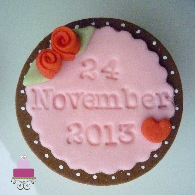 Cupcake covered in pink fondant with a date imprinted on it and accented with tiny rolled fondant roses and leaves