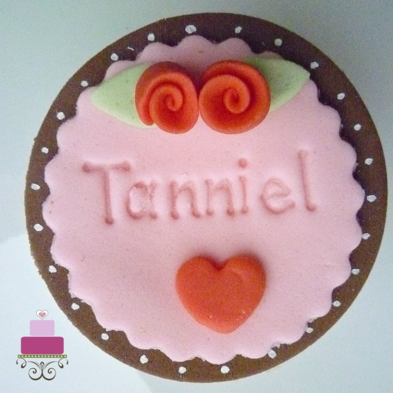 Cupcake decorated in pink with the baby name imprinted on and accented with tiny red fondant roses
