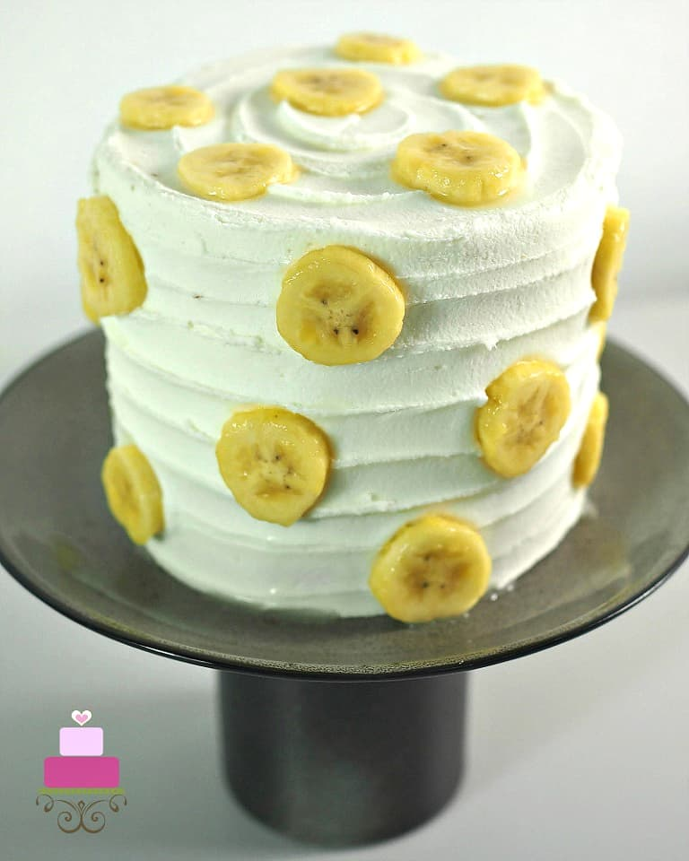 A round cake decorated with white frosting and fresh banana slices. Cake is on a black cake stand