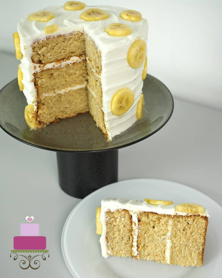 A round cake on a black cake stand decorated with banana slices. A slice of the cake is cut out onto a white plate