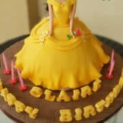 A doll cake decorated in yellow gown and a stalk of rose like Belle from Beauty and the Beast