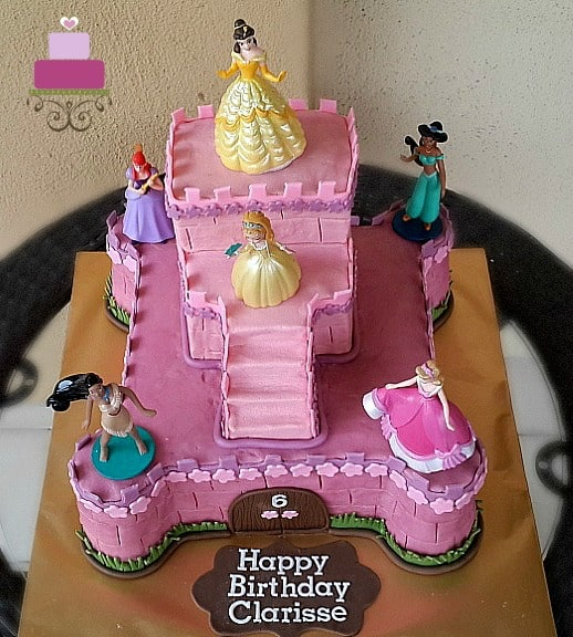 A two tier castle cake in pink, decorated with 6 Disney princess toy toppers