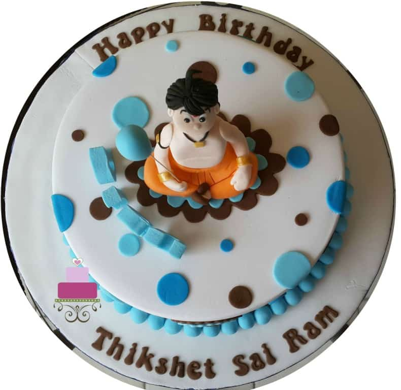 A round cake with blue and brown polka dots and Chhota Bheem cake topper holding a blue balloon.