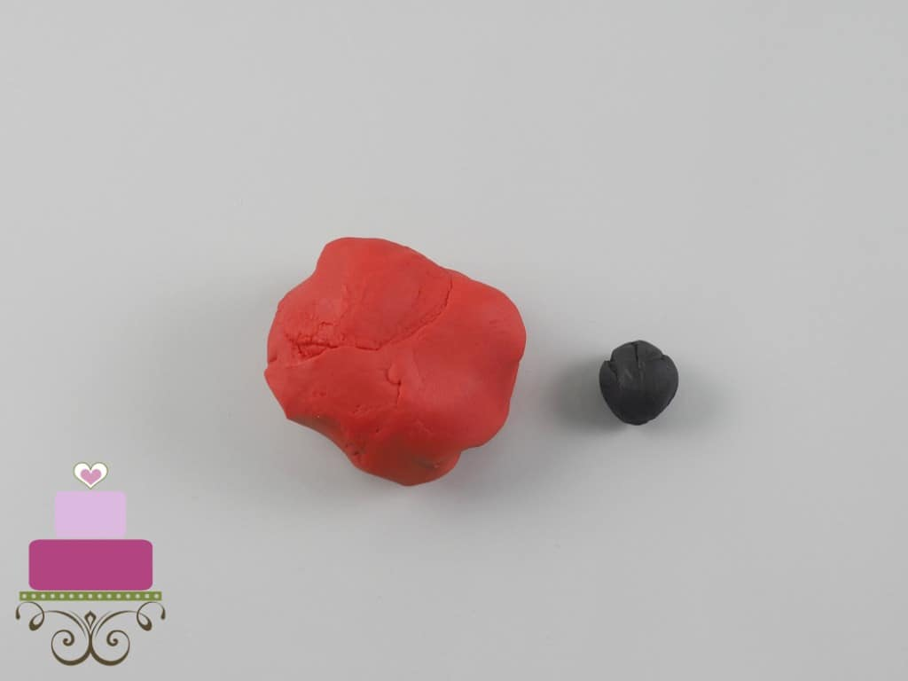 A lump of red fondant and a small lump of black fondant