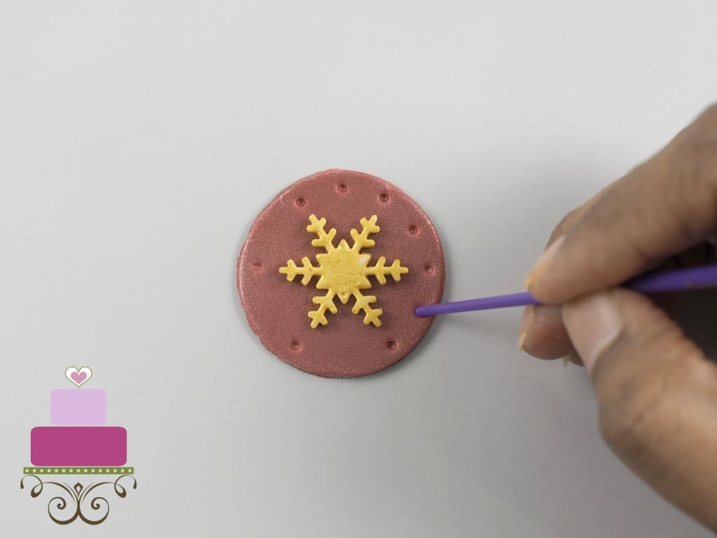 Poking holes with the back of a paint brush on a round maroon fondant cut out