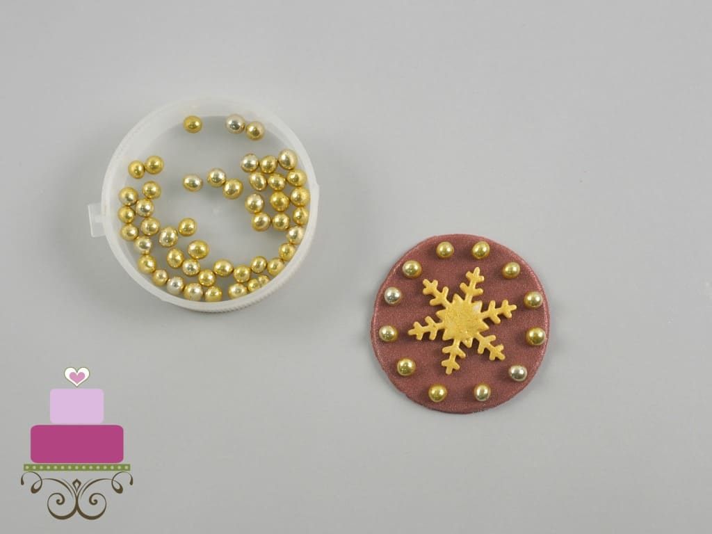 A round maroon fondant cut out with a gold snowflake and gold bead frame