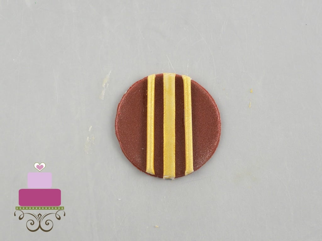 A round maroon fondant cut out with gold lines on it