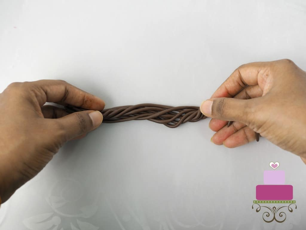 Twisting a group of brown fondant strips with hands