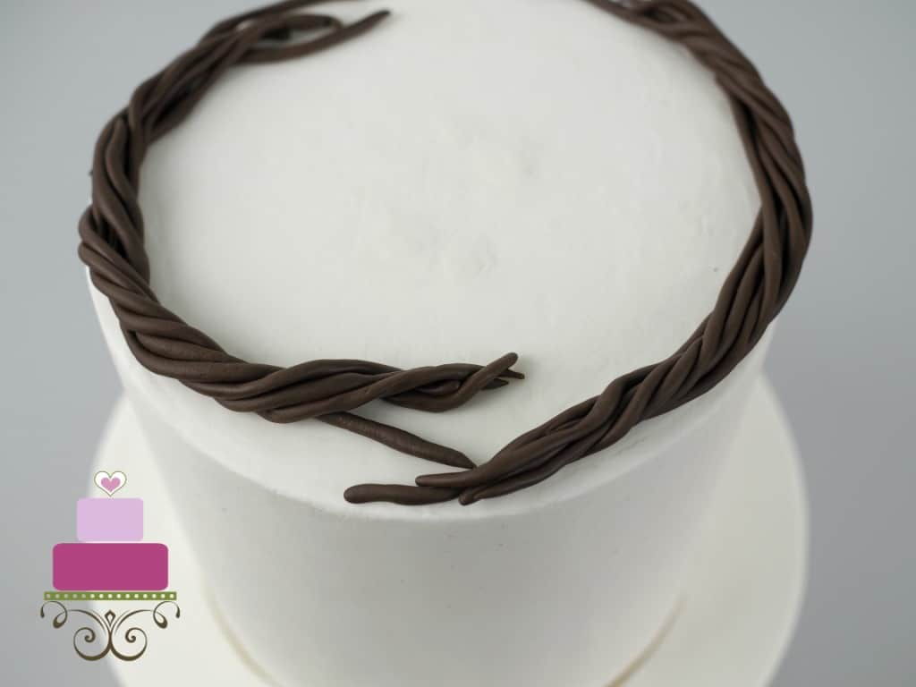 Fondant twigs garland on a white cake