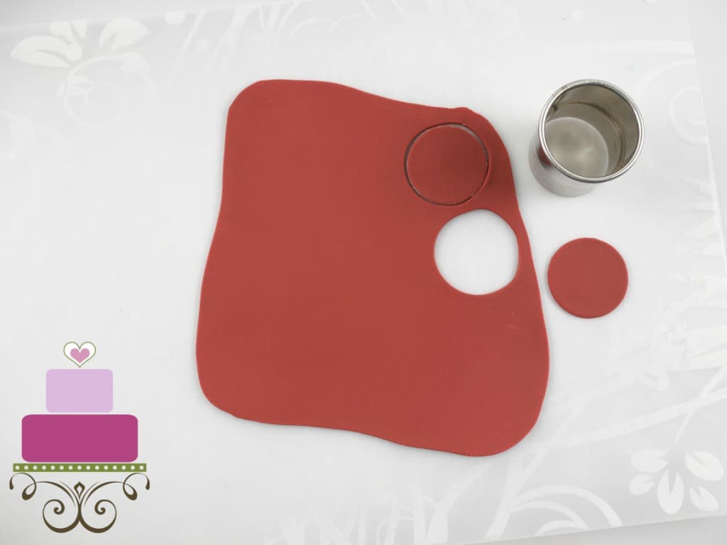 A rolled piece of maroon fondant with a round cutter on the side