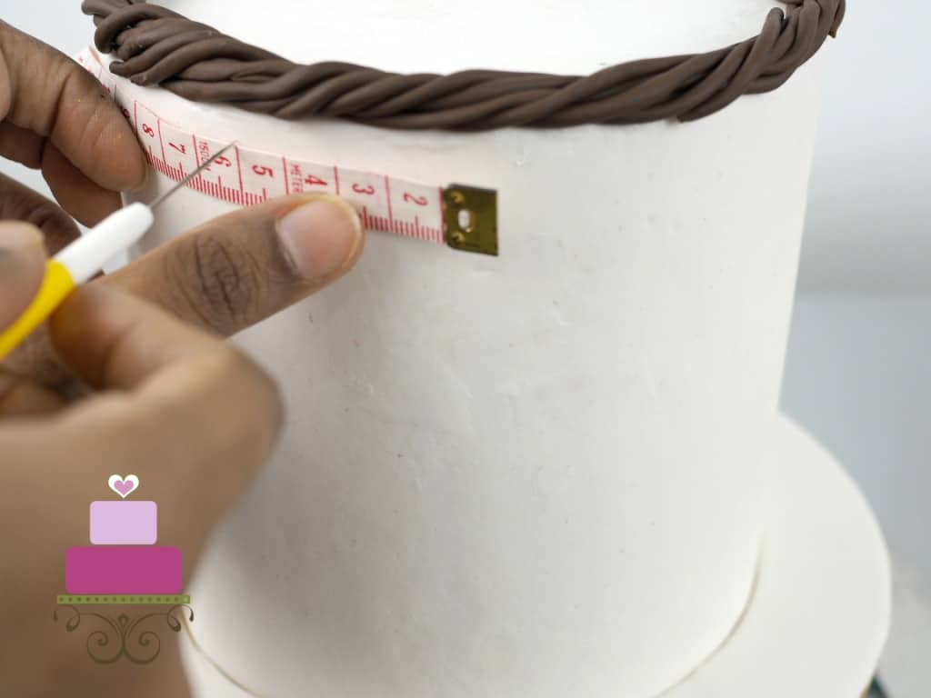 Using a measuring tape and needle tool to mark a cake