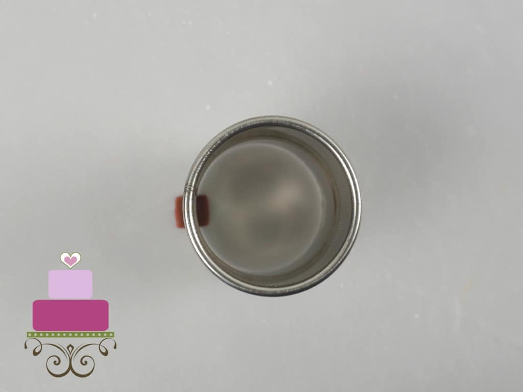 Using a round cutter to cut a small piece of maroon fondant