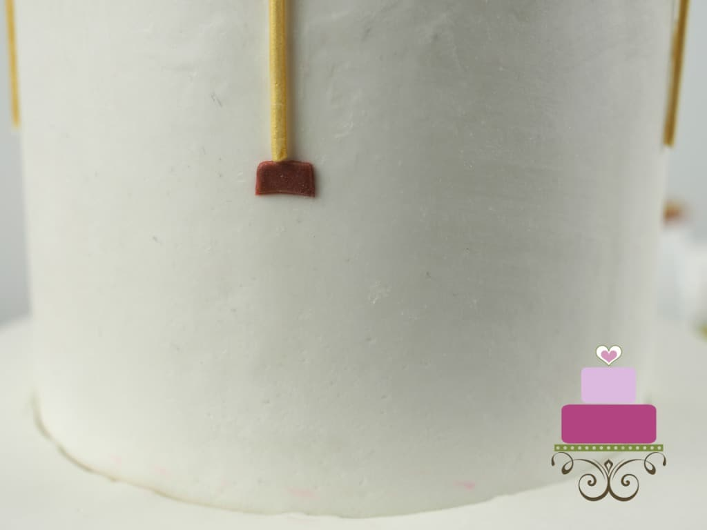 A long gold strip of fondand attached to a small rectangle piece of maroon fondant on a white cake