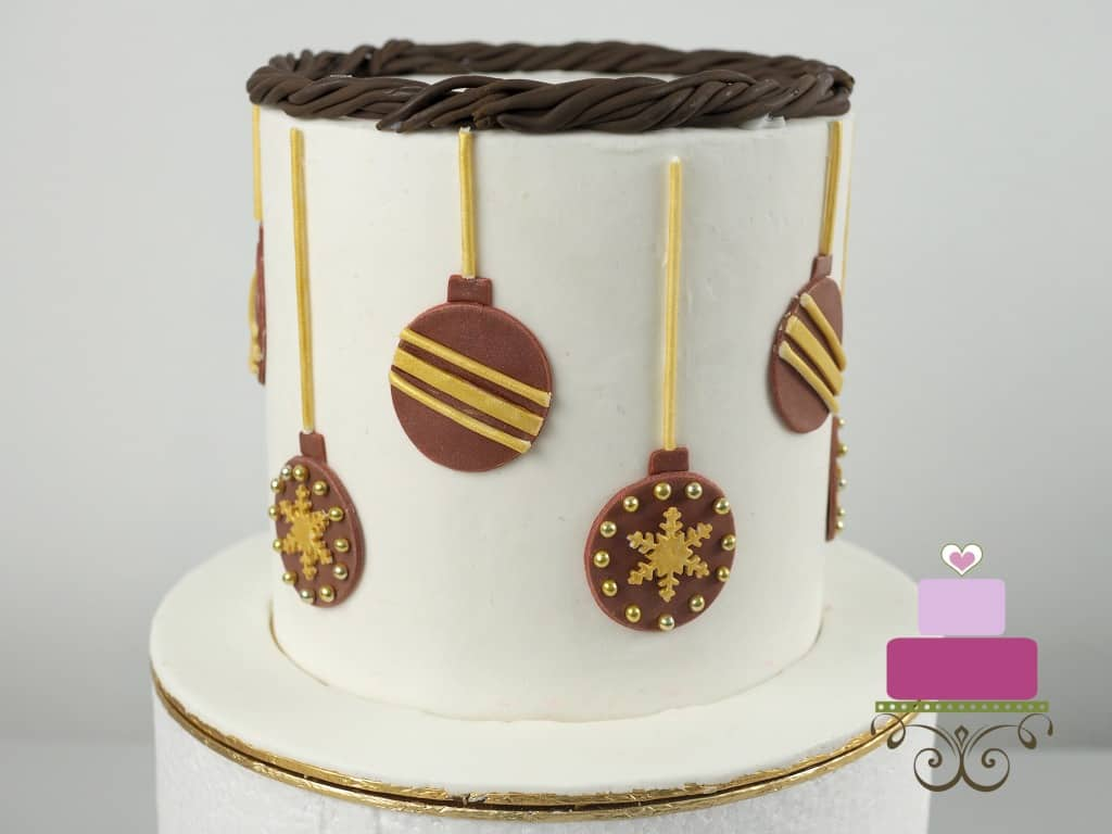 A round cake decorated with maroon baubles.