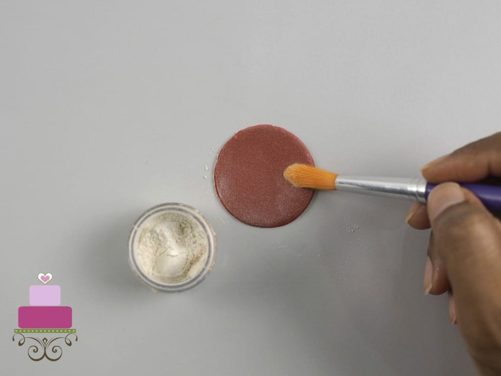Brushing a round maroon cut out with luster dust