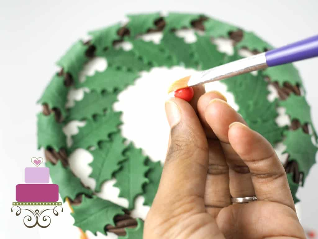 Attaching fondant holly berries to a cake