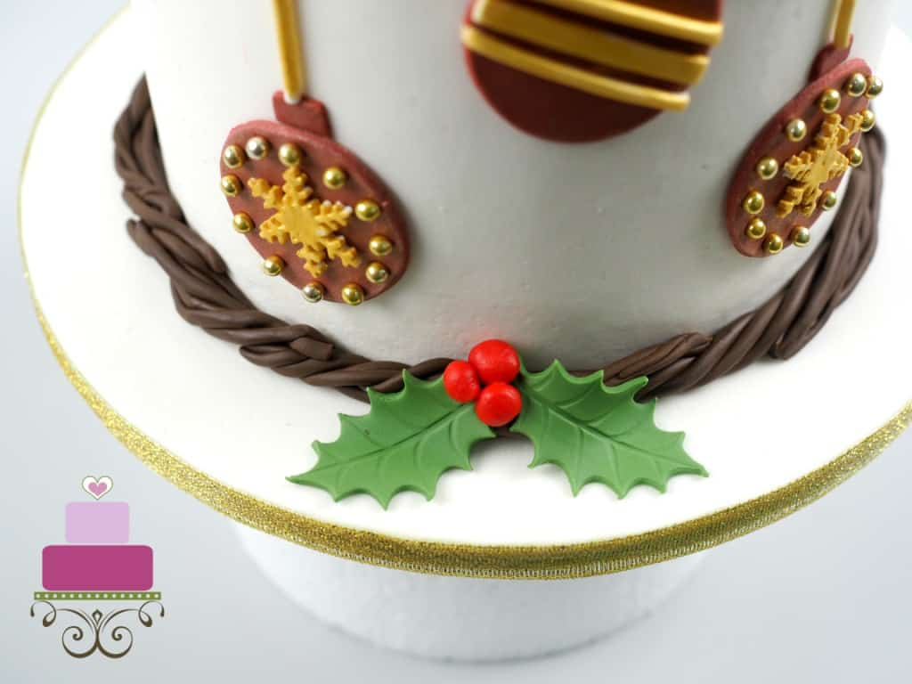 Cake border made of fondant twigs garland and holly berries and leaves