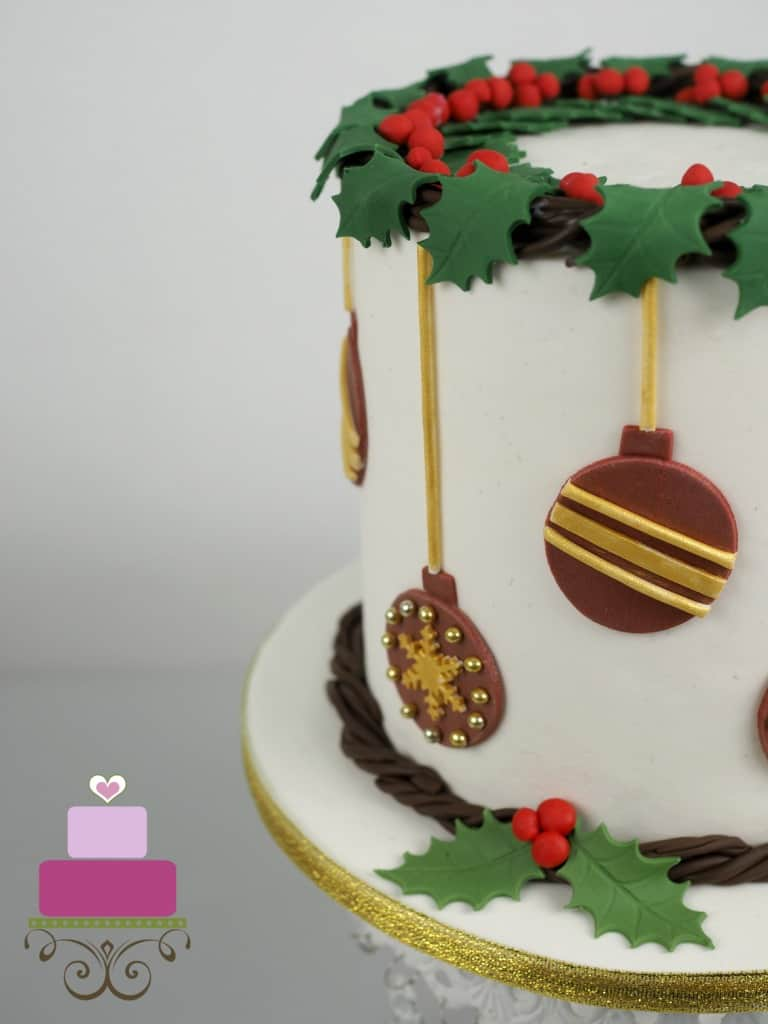 A round cake decorated with holly garland and fondant baubles.