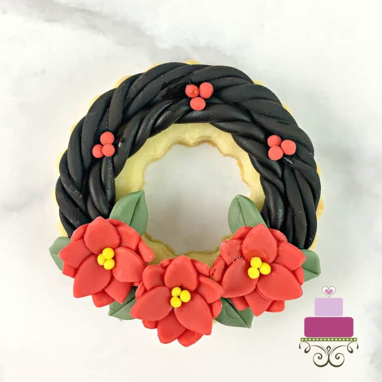 Cookies decorated to look like poinsettia wreaths