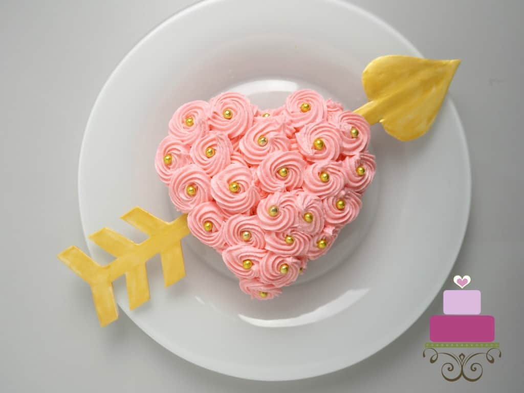 A mini heart shaped cake covered in pink buttercream rosettes and gold beads and a paper heart going through the sides