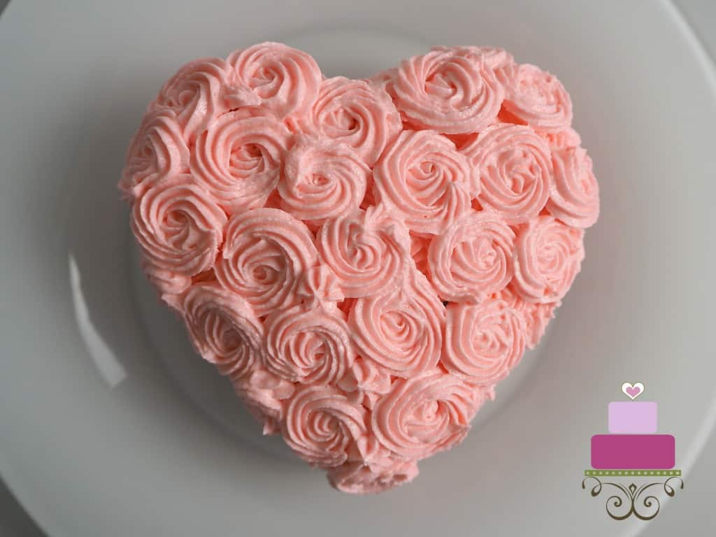 A mini heart shaped cake covered in pink buttercream rosettes