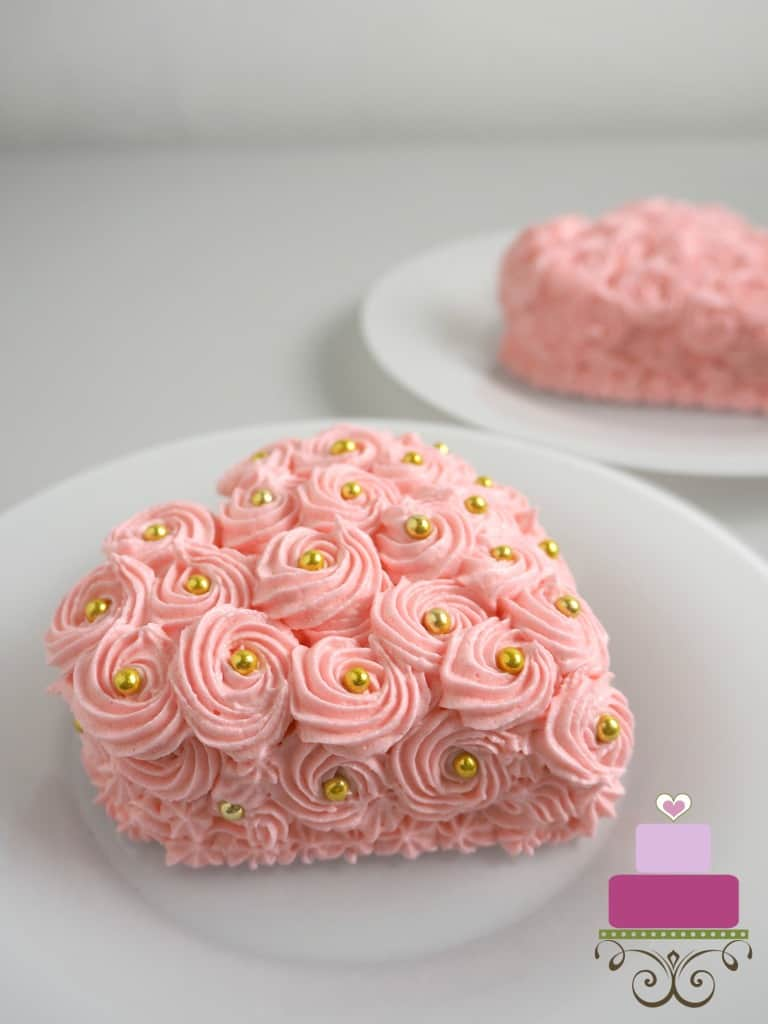 A mini heart shaped cake covered in pink buttercream rosettes and gold beads
