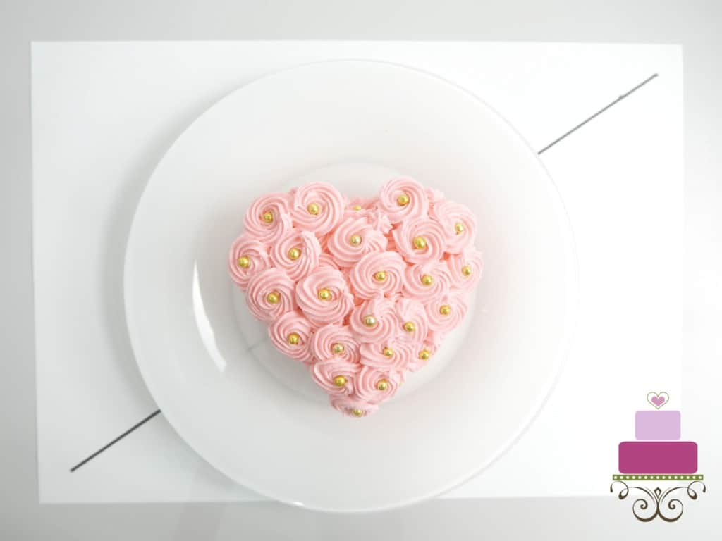 A mini heart shaped cake covered in pink buttercream rosettes on a white plate, against a white paper background