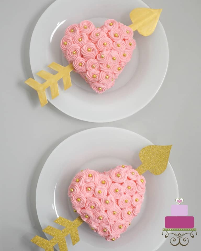 Two mini heart shaped cakes covered in pink buttercream rosettes and gold beads and paper heart going through the sides