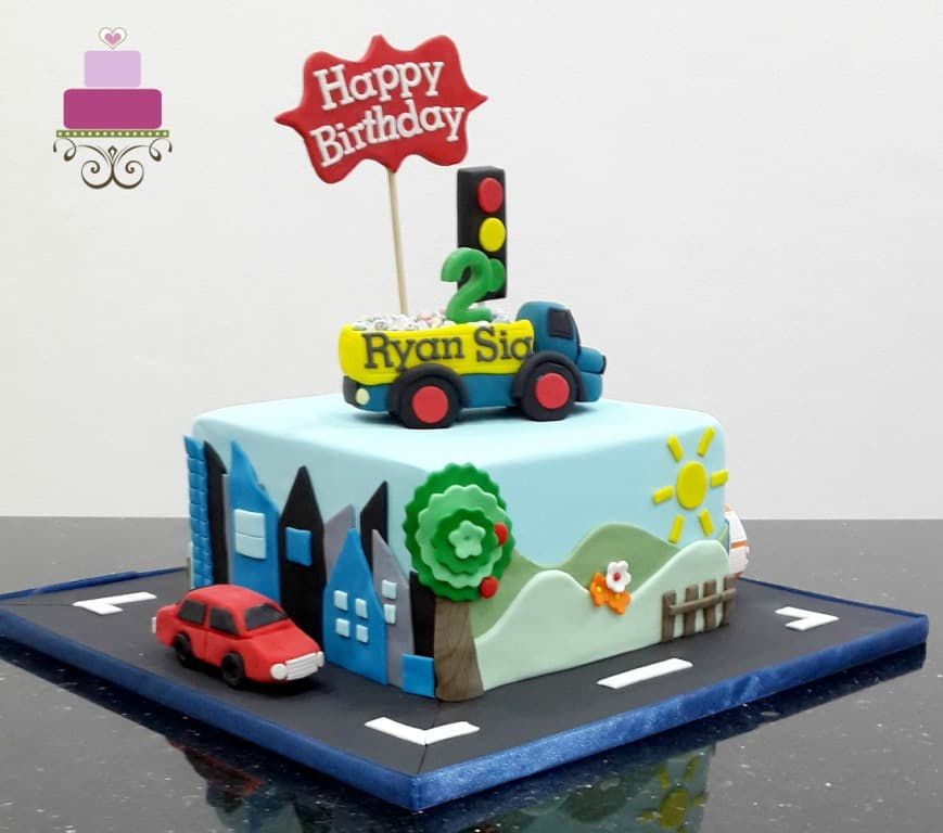 A square cake with a dump truck cake topper. Cake is decorated with scenery on the sides and a fondant car on the cake board.