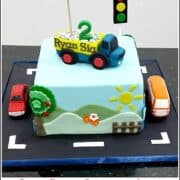 A square cake with a dump truck cake topper. Cake is decorated with scenery on the sides and a fondant car and bus on the cake board.