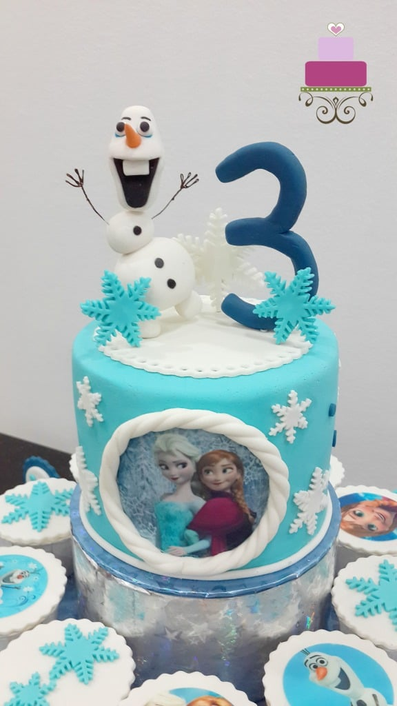 A round blue cake with 3d Olaf cake topper, a number three topper and snowflakes. On the front side is an image of Anna and Elsa in edible sugar sheet.