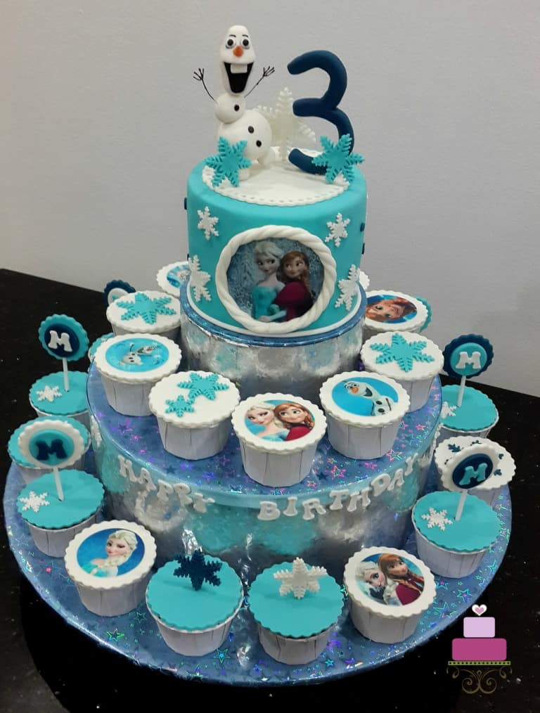 A blue round cake with 3d Olaf topper on a cupcake stand, with cupcakes on the stand