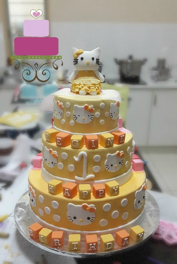 A 3 tier hello kitty cake in yellow, with Hello Kitty cake topper