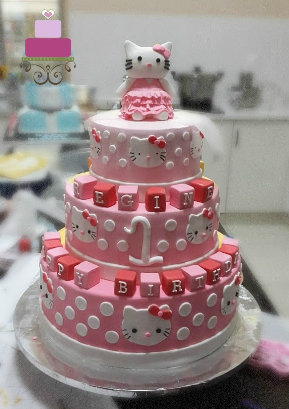 A 3 tier hello kitty cake in pink, with Hello Kitty cake topper