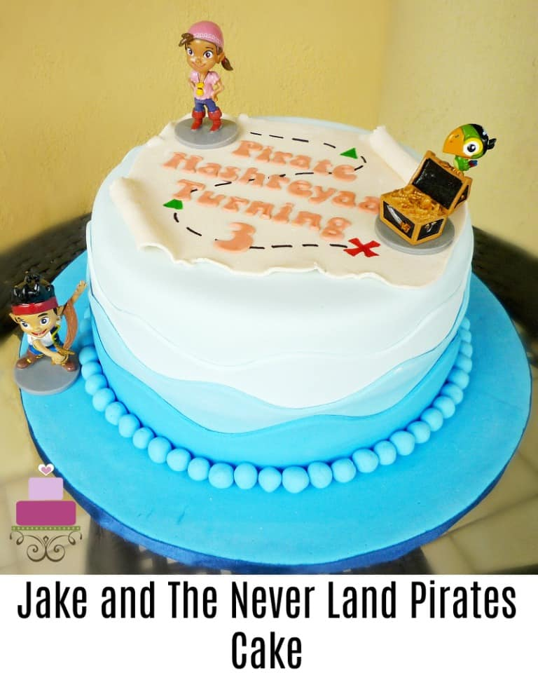 A round cake with a fondant pirate map and Jake and the Neverland Pirates toy toppers
