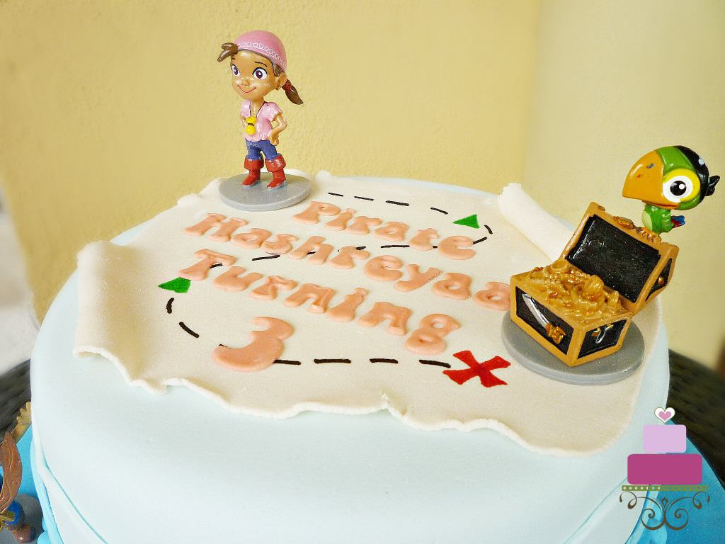 A pirate map cake topper with toy toppers in Jake and the Neverland Pirates characters