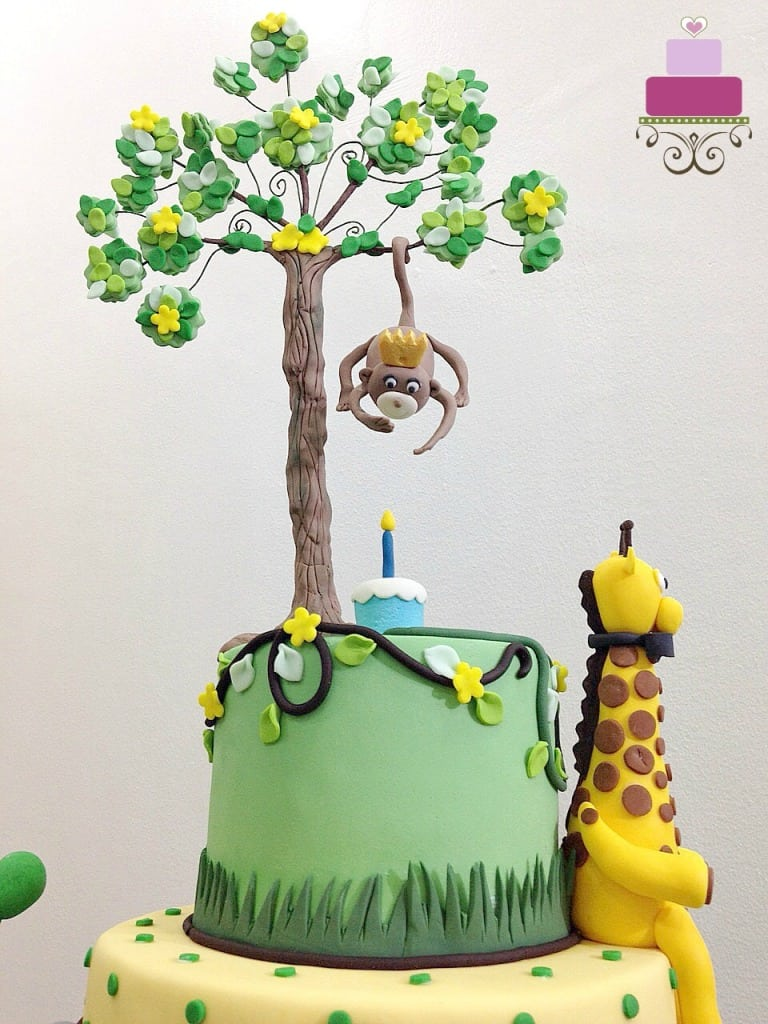 3D fondant giraffe with a bow, sitting on a cake