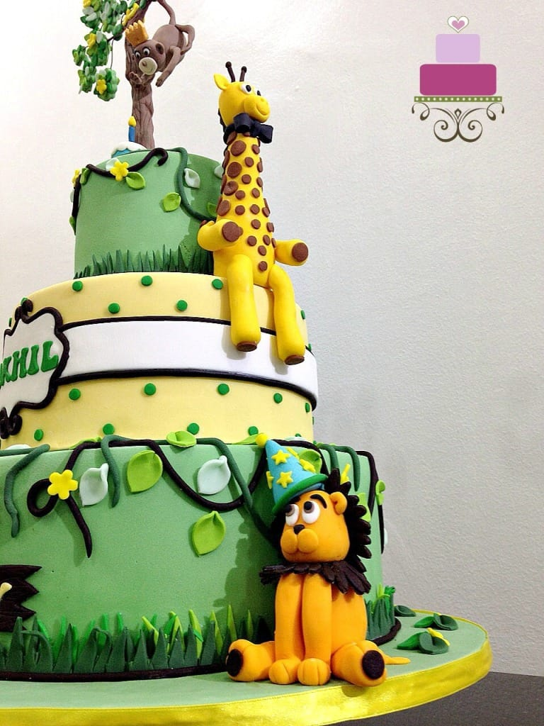 A yellow fondant giraffe and lion with a party hat on the sides of a 3 tier cake