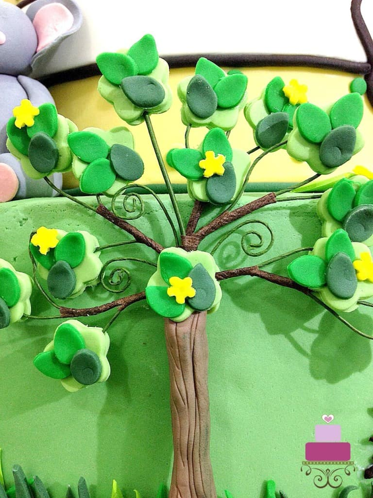 Fondant tree on the side of a green cake