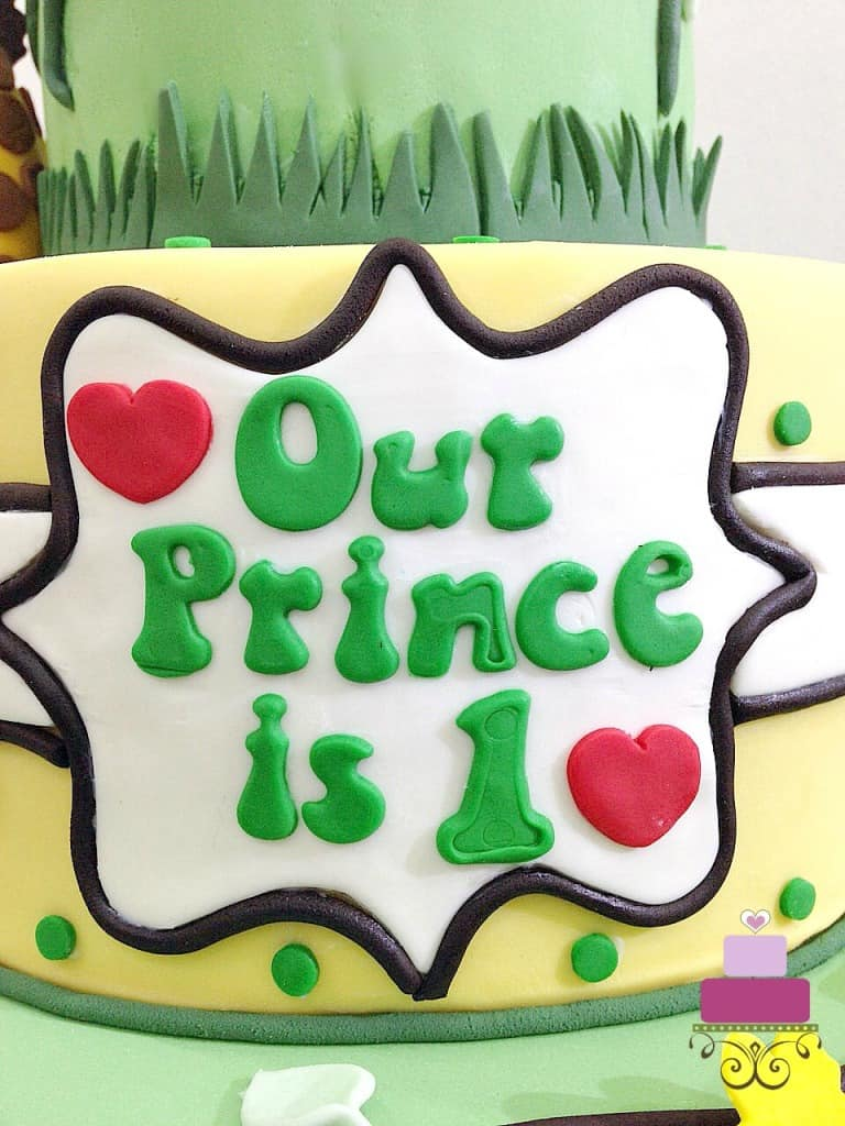 """our prince is 1"" fondant plaque on a cake"
