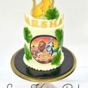 A round double barrel cake decorated with Simba cake topper, Lion King edible image and green fondant palm leaves